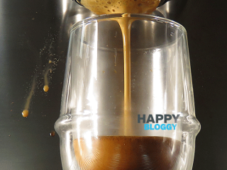 Image displaying espresso pour with bubbles